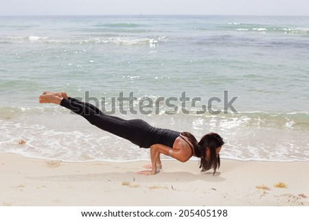 Stock image of woman balancing on her arms by the shore - stock photo