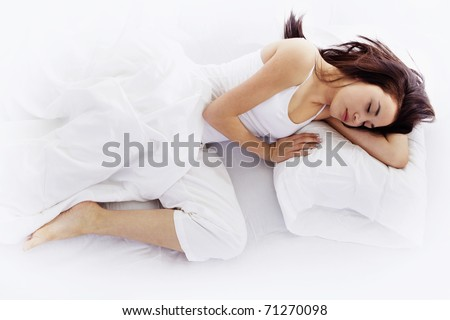 Stock image of young woman sleeping on white bed - stock photo