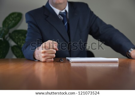 Stock image with businessman in the office who has put his fist on the table. This is a meeting room during a meeting. He defends his assertion.