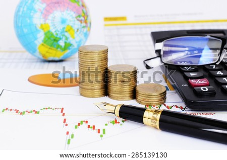 Stock investment concept with fountain pen and coins stack and calculator and eyeglasses on stock chart report