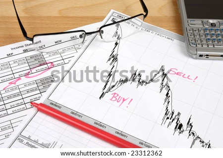 Stock market candle charts, remarks with a red marker, glasses and mobile smart phone - stock photo