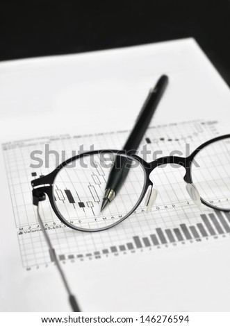 Stock market charts, eyeglasses, and machanical pencil - stock photo