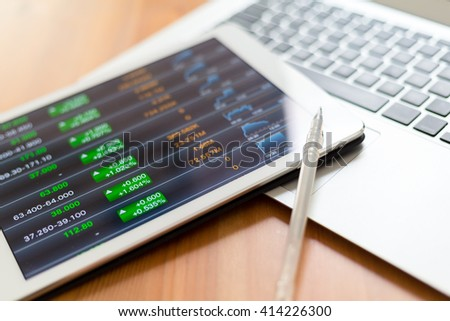 Stock market graph with tablet pc and laptop - stock photo