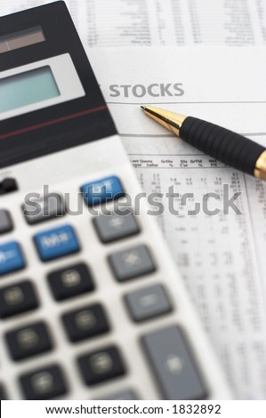 Stock market table analysis, calculator and pen indicates research and analysis, vertical orientation, pen pointing to word stocks, shallow depth of field - stock photo
