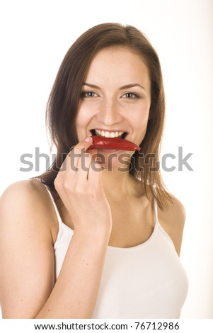 stock photo closeup portrait of a happy young woman holding red hot chili in mouth