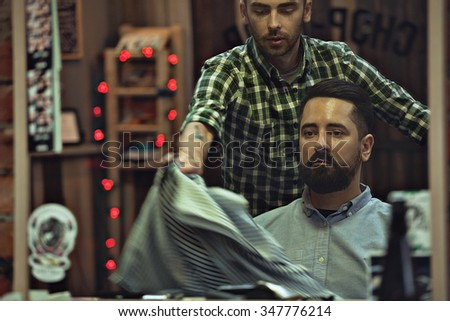 Stock photo male barbershop customer, after clipping a mustache and beard, the stylist removes the cloak robe with satisfied customers. The client in Barbershop after the procedure looks in the mirror - stock photo