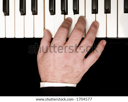 Stock photo of a closeup of a man's hands playing a piano.