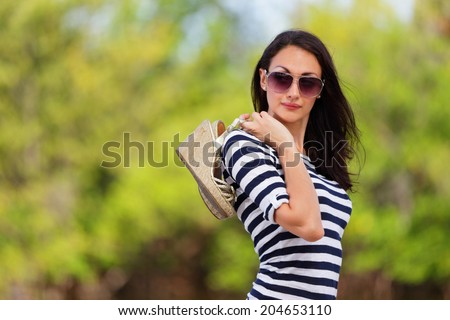 Stock photo of a fashion model holding her shoes over her shoulder - stock photo