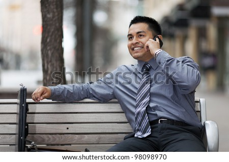Stock photo of a smiling Hispanic businessman sitting on a city bench in a business district with an open briefcase, while he talks on a cell phone. - stock photo