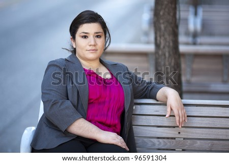 Stock photo of a well dressed businesswoman relaxing on a city bench alongside a downtown street.