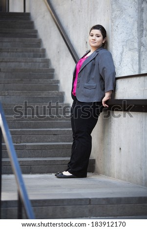 Stock photo of a well dressed businesswoman taking a break and leaning on the railing of a staircase.