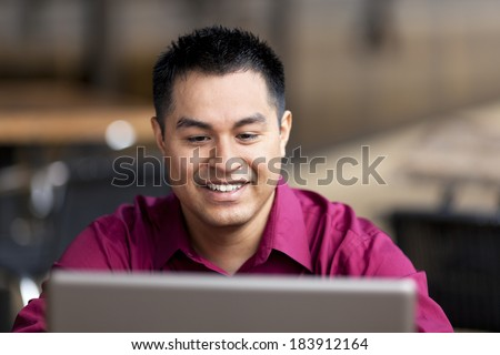 Stock photo of a well dressed Hispanic businessman looking down at a laptop while telecommuting from an internet cafe. - stock photo