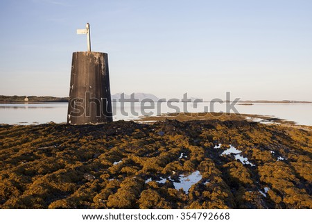 Stock photo of fixed unlighted concrete daymark at rocky islet at low tide. Photographed at Norwegian coast.  - stock photo