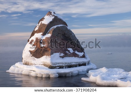 Stock photo of one big stone in the sea, half covered with fresh snow. Cold winter day, evaporating sea, white clouds at sky. - stock photo