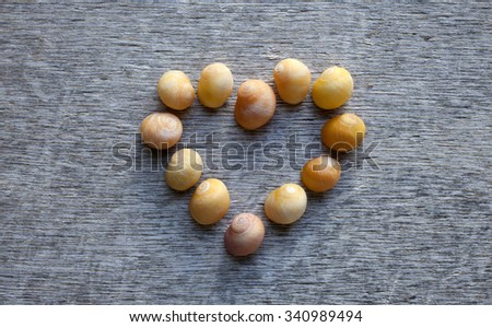 Stock photo of small yellow sea snail shells arranged in heard form at gray wooden background. - stock photo
