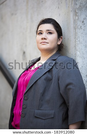 Stock portrait photo of a well dressed businesswoman leaning on a concrete wall.