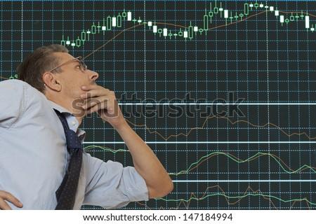 Stock trader looking at monitors  - stock photo