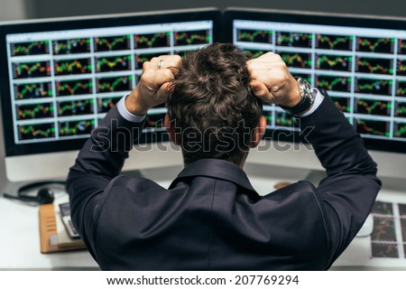 Stock trader tearing out his hair from despair, rear view - stock photo