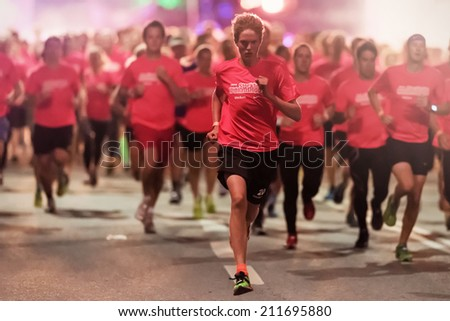 STOCKHOLM - AUG, 16: A focused runner in one of the many groups of the Midnight Run (Midnattsloppet) event. Aug 16, 2014 in Stockholm, Sweden - stock photo