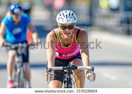 STOCKHOLM - AUG 23, 2015: Amateur triathlete cyclist in front view with happy face at the ITU World Triathlon event in Stockholm. - stock photo