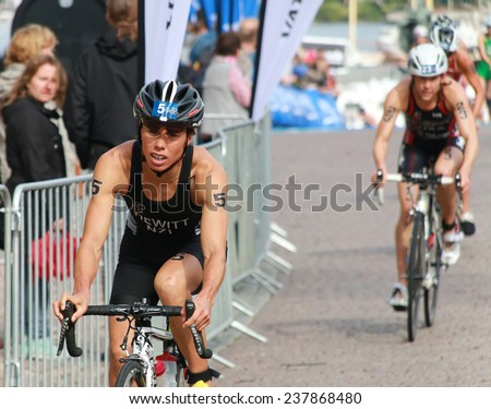 STOCKHOLM - AUG 23: Andrea Hewitt (NZL) cycling after the transition in the Women's ITU World Triathlon series event August 23, 2014 in Stockholm, Sweden - stock photo