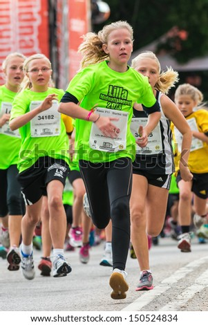 STOCKHOLM - AUG, 17: Capture of girl running in the Midnight Run for children (Lilla Midnattsloppet) event, a group of excited children running. Aug 17, 2013 in Stockholm, Sweden