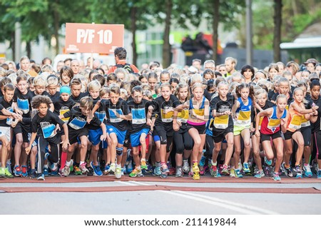 STOCKHOLM - AUG, 16: Closeup of the chaotic start when the young kids runs in the Midnight Run for children (Lilla Midnattsloppet) event. Aug 16, 2014 in Stockholm, Sweden
