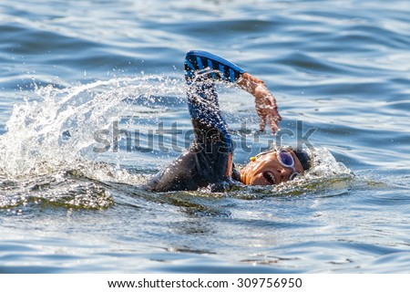 STOCKHOLM - AUG 22, 2015: Face of a female triathlete swimming and gasping for air at Womens ITU World Triathlon series event. - stock photo