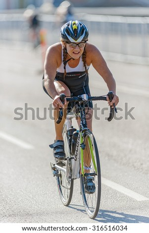 STOCKHOLM - AUG 23, 2015: Female triathlete on a bicycle outside the town hall in the ITU World Triathlon event in Stockholm. - stock photo
