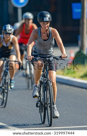 STOCKHOLM - AUG 23, 2015: Female triathlete on the citybike at the ITU World Triathlon event in Stockholm.