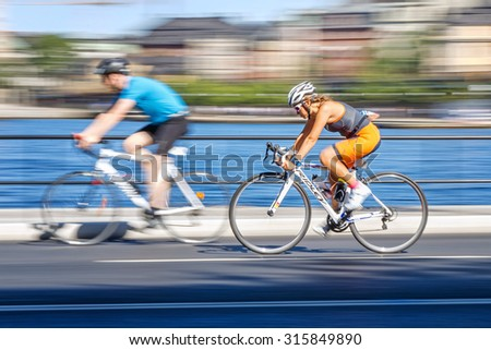STOCKHOLM - AUG 23, 2015: Female triathlete passing a rider in the cycling part with motion blur of the panning at the ITU World Triathlon event in Stockholm. - stock photo
