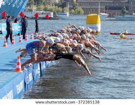 STOCKHOLM - AUG 22, 2015: Group of male swimming competitors in colorful swimsuits juming into the water in the Men's ITU World Triathlon series event August 22, 2015 in Stockholm, Sweden - stock photo