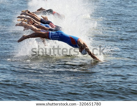 STOCKHOLM - AUG 22, 2015: Group of male swimming competitors in colorful swimsuits jumping into the water in the Men's ITU World Triathlon series event August 22, 2015 in Stockholm, Sweden - stock photo