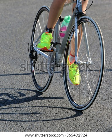 STOCKHOLM - AUG 23, 2015: Legs and feet of a cycling woman with yellow shoes at ITU World Triathlon event in Stockholm, 2015 - stock photo