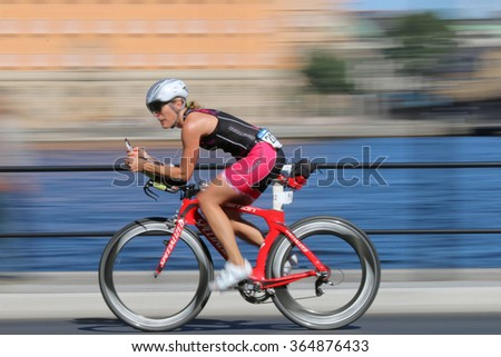 STOCKHOLM - AUG 23, 2015: Rapid cycling woman on advanced red racing bike, the speed makes it un-sharp at ITU World Triathlon event in Stockholm, 2015