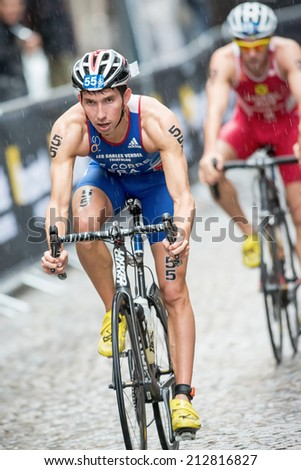 STOCKHOLM - AUG, 23: Triathlete Pierre Le Corre frome France cycling in heavy rain at the cobblestone road in the Mens ITU World Triathlon Series event August 23, 2014 in Stockholm, Sweden
