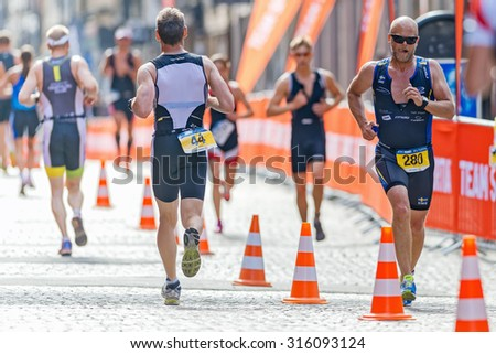 STOCKHOLM - AUG 23, 2015: Triathletes running at the cobblestones in the old town at the ITU World Triathlon event in Stockholm. - stock photo