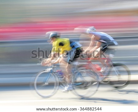STOCKHOLM - AUG 23, 2015: Two rapid cycling men on a black, the speed makes it un-sharp at ITU World Triathlon event in Stockholm, 2015 - stock photo