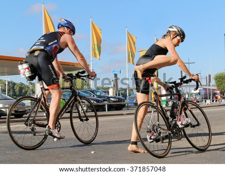 STOCKHOLM - AUG 23, 2015: Woman and man jumping up on the bicycles in the triathlon transition zone at ITU World Triathlon event in Stockholm, 2015 - stock photo