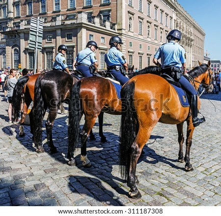 STOCKHOLM - AUGUST 10, 2015: Female mounted patrol secures Changing of the Guard at the Royal Palace. The Royal Guard was established in 1523 and continuously guards the Royal Palace since then. - stock photo