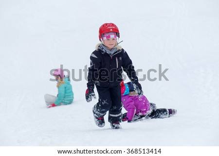 STOCKHOLM - JAN 24, 2016: Three kids wearing helmets playing in a snowy slope at the Stockholm Ski Marathon event January 24 2016 in Stockholm, Sweden - stock photo