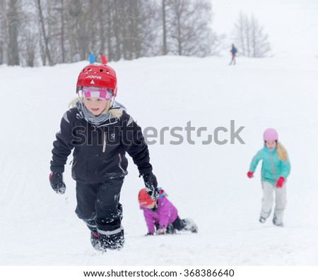 STOCKHOLM - JAN 24, 2016: Three kids wearing helmets playing in a snowy slope, trees in the background at the Stockholm Ski Marathon event January 24 2016 in Stockholm, Sweden - stock photo