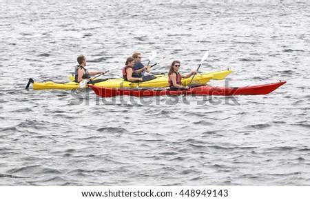 STOCKHOLM - JUL 02, 2016: Red and yellow canoes with officials before the start signal in the Women's ITU World Triathlon series event July 02, 2016 in Stockholm, Sweden
