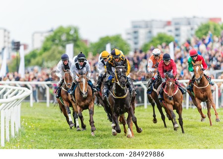 STOCKHOLM - JUNE 6: Action when jockeys and horses coming out from the last curve at the Nationaldags Galoppen at Gardet. June 6, 2015 in Stockholm, Sweden.