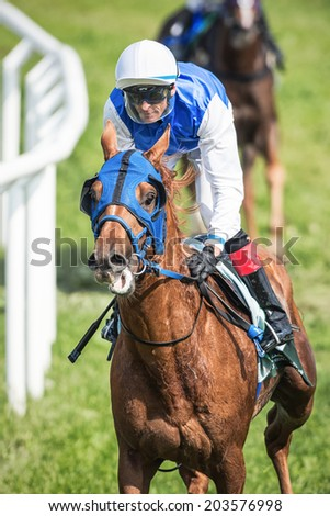 STOCKHOLM - JUNE 6: Closeup of a jockey after a curve at the Nationaldags Galoppen in Gardet. June 6, 2014 in Stockholm, Sweden. - stock photo