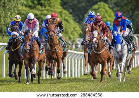 STOCKHOLM - JUNE 6: Group of colorful jockeys and horses in fast pace during the race at the Nationaldags Galoppen at Gardet. June 6, 2015 in Stockholm, Sweden. - stock photo