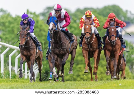 STOCKHOLM - JUNE 6: Group of jockeys and horses in fast pace during the race at the Nationaldags Galoppen at Gardet. June 6, 2015 in Stockholm, Sweden. - stock photo