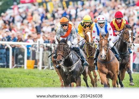 STOCKHOLM - JUNE 6: Jockeys into last curve at the Nationaldags Galoppen in Gardet. June 6, 2014 in Stockholm, Sweden. - stock photo