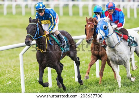 STOCKHOLM - JUNE 6: Three jockeys out of the fourth curve at the Nationaldags Galoppen in Gardet. June 6, 2014 in Stockholm, Sweden. - stock photo