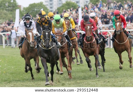 STOCKHOLM - JUNE 06: Tough race between the race horses and jockeys in colorful clothes at the Nationaldags Galoppen at Gardet. June 6, 2015 in Stockholm - stock photo